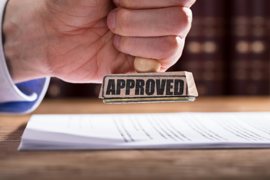 "poslovni kredit poslovni zajam poslovni plan odobravanje kredita muškarac udara pečat ""odobreno"""